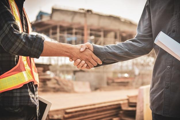 Ingénieur deux personnes serrent la main projet d'accord immobilier construction de bâtiments