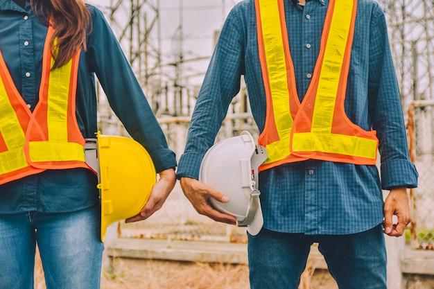 Ingénieur deux personnes tenant un casque portent une combinaison de sécurité