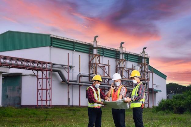 Ingénieur discute de la documentation technique avec son aide sur le territoire d'une centrale moderne. ingénieurs travaillant dans la zone de la centrale électrique