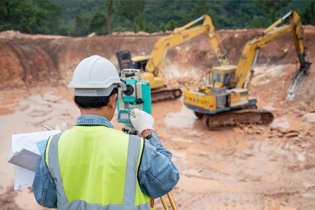Un ingénieur du chantier en construction utilise le théodolite pour vérifier les travaux de fondation des excavations