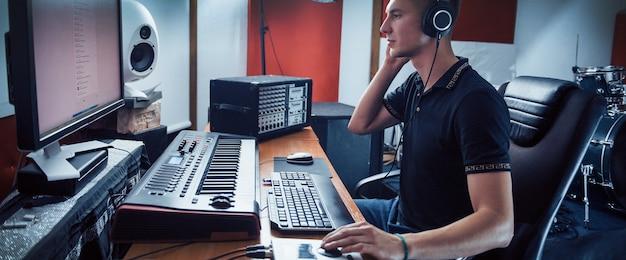 Ingénieur du son au casque travaillant et mixant de la musique à l'intérieur du studio.