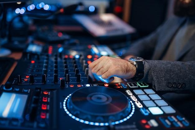 L'ingénieur du son remet le panneau de commande à distance dans le studio d'enregistrement.