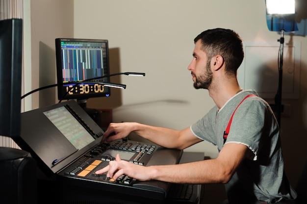 Un ingénieur d'éclairage travaille avec les techniciens d'éclairage sur le contrôle du spectacle de concert. mélangeur d'éclairage professionnel, console de mixage. matériel pour concerts.