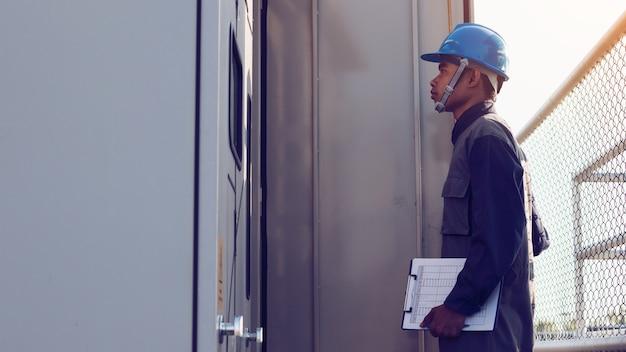 Ingénieur ou électricien vérifiant l'état intensifier le transformateur haute tension