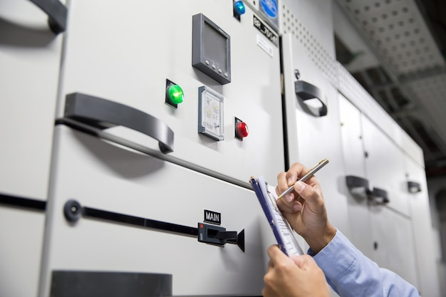Ingénieur électricien vérifiant la tension du courant électrique au disjoncteur du panneau de commande du démarreur de l'unité de traitement d'air (cta) pour le climatiseur.
