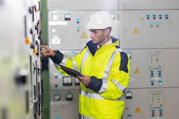 L'ingénieur électrique de l'homme tient le système électrique de surveillance de la tablette dans l'inspection du technicien de la salle de contrôle