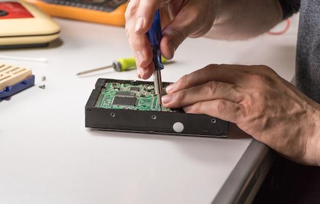 L'ingénieur en électronique répare le disque dur de l'ordinateur. un technologue avec un tournevis démonte le disque dur
