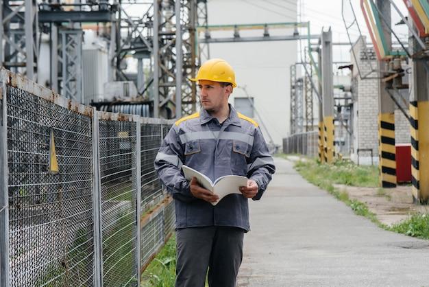 L'ingénieur en énergie inspecte l'équipement de la sous-station.