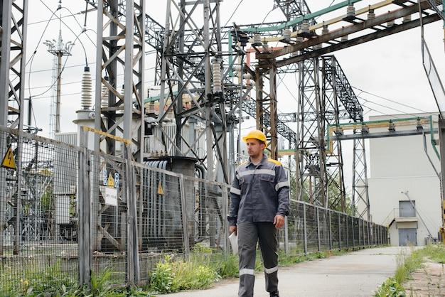 Un ingénieur en énergie inspecte l'équipement de la sous-station