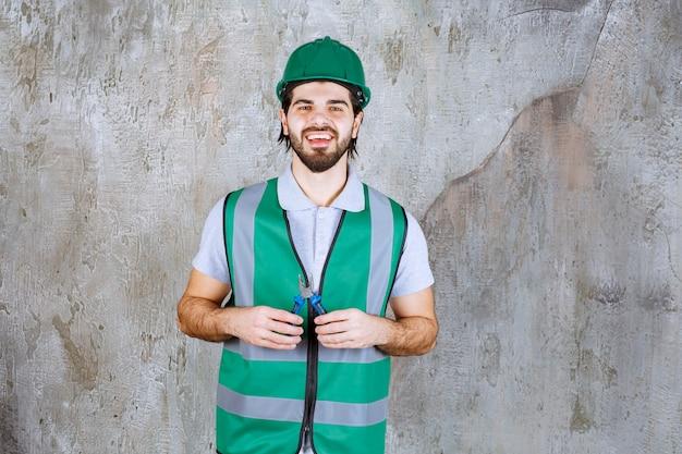 Ingénieur en équipement jaune et pinces de maintien de casque.