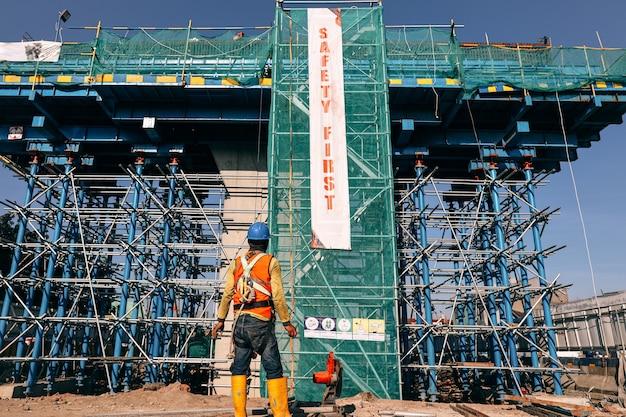 Ingénieur en équipement de protection de sécurité debout devant le bâtiment en construction