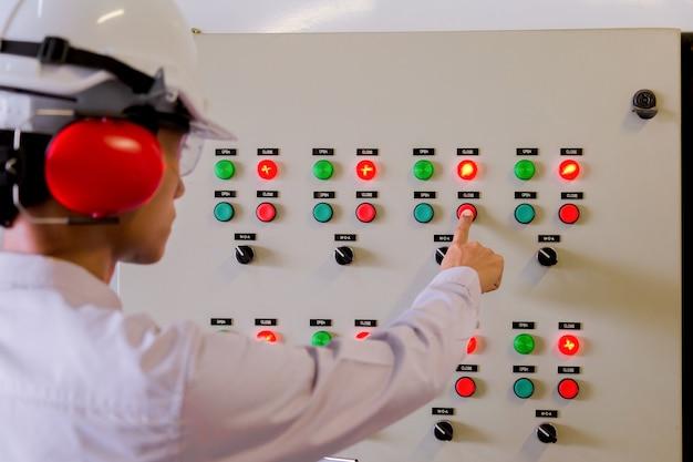 L'ingénieur est en train de vérifier le panneau de commande électrique en usine / le panneau de commande système prêt.