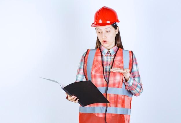 Ingénieur féminin en casque rouge tenant un plan de projet noir et semble confus.