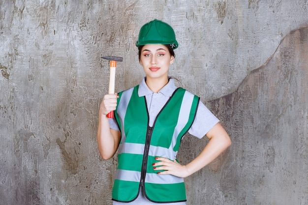 Ingénieur féminin en casque vert tenant une hache à manche en bois pour un travail de réparation