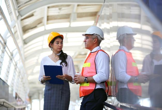 Ingénieur féminin avec collègue tenant le plan contre le chantier de construction