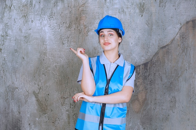 Ingénieur féminin portant un casque bleu et un équipement et pointant quelque chose sur la gauche avec des émotions