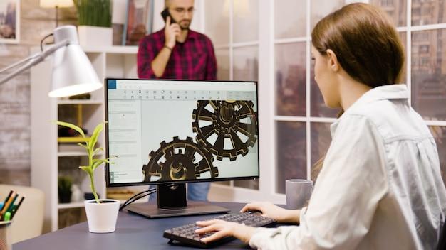 Ingénieur féminin travaillant sur une conception 3d de la maison. le petit ami en arrière-plan entre dans la pièce et parle au téléphone.