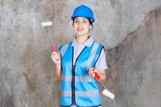 Ingénieur féminin en uniforme bleu et casque tenant un rouleau de finition pour la peinture