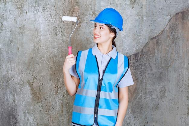 Ingénieur féminin en uniforme bleu et casque tenant un rouleau de finition pour la peinture.