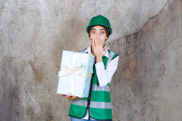 Ingénieur féminin en uniforme vert et casque tenant une boîte-cadeau bleue et semble confus et terrifié.