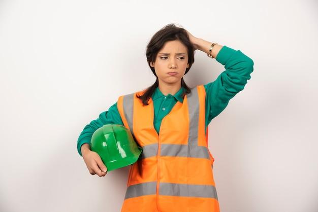 Ingénieur femme bouleversée se gratter la tête et tenant un casque sur fond blanc