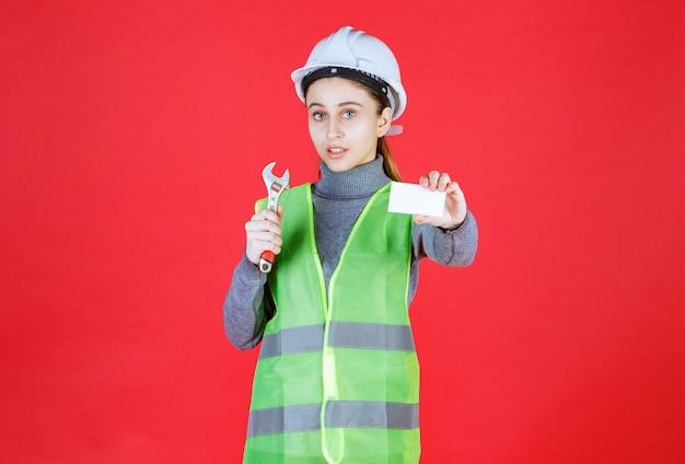 Ingénieur femme avec casque blanc tenant une clé métallique et présentant sa carte de visite.
