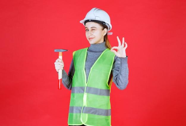 Ingénieur femme avec casque blanc tenant une hache en bois et montrant le signe de la main de plaisir.