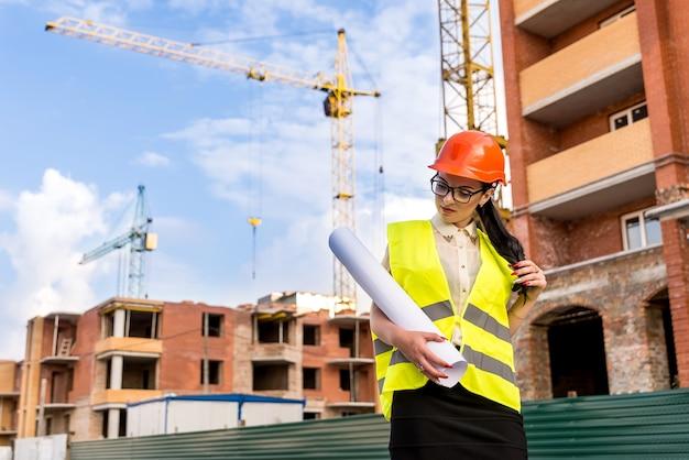 Ingénieur femme en casque avec rouleaux sur chantier