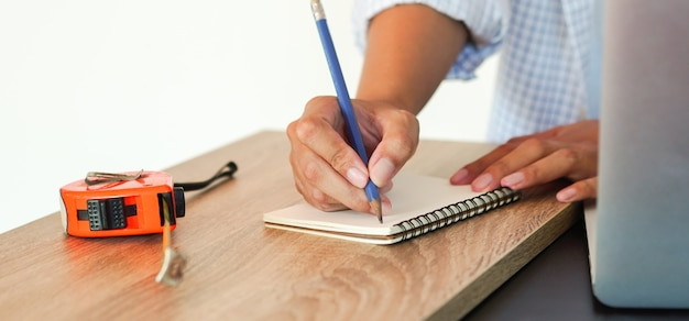 Ingénieur femme esquisse conception sur le cahier de pages avec mesure à la maison