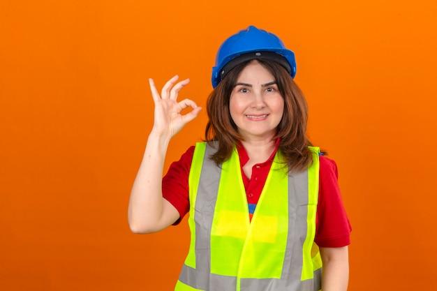 Ingénieur femme portant un gilet de construction et un casque de sécurité avec un grand sourire sur le visage faisant signe ok debout sur un mur orange isolé