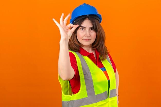 Ingénieur femme portant un gilet de construction et un casque de sécurité avec un sourire confiant faisant signe ok debout sur un mur orange isolé