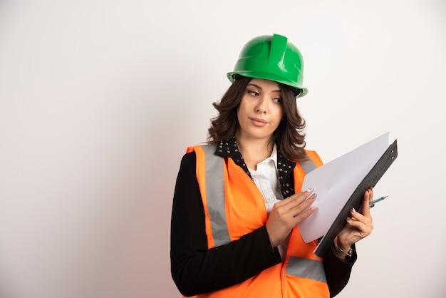 Ingénieur de femme regardant par l'ordinateur portable sur le blanc