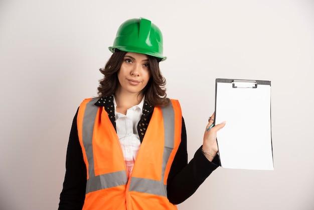 Ingénieur femme tenant le presse-papiers sur blanc