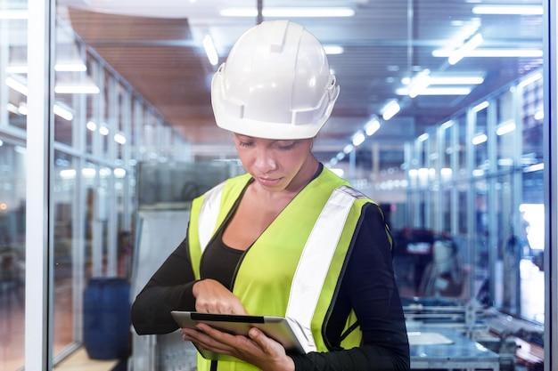 Ingénieur femme utilisant une tablette pour vérifier sur le lieu de travail femme portant une suite de travail