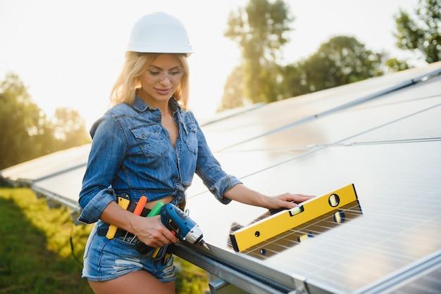Ingénieur de femmes travaillant sur la vérification de l'équipement à la centrale solaire d'énergie verte