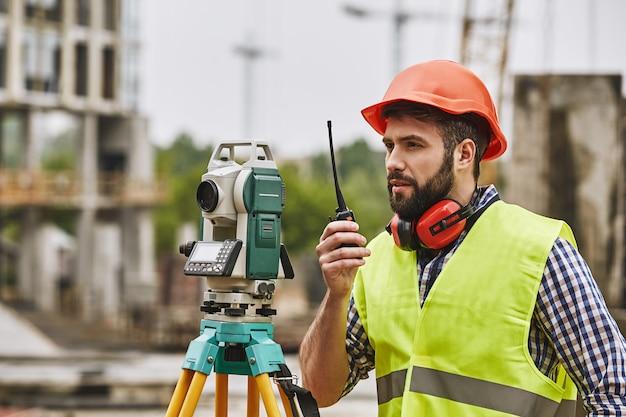 Ingénieur géomètre de mesures précises en tenue de protection et casque rouge à l'aide d'équipement géodésique