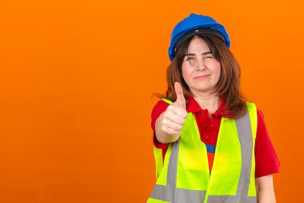 Ingénieur en gilet de construction et casque de sécurité clignotant montrant le pouce vers le haut souriant sur mur orange isolé