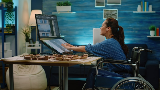 Ingénieur handicapé utilisant un écran tactile pour le modèle de construction