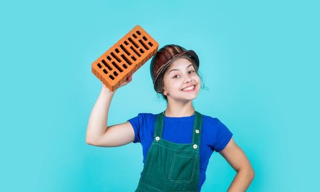 Ingénieur heureux d'enfant avec la brique dans le casque, entrepreneur.