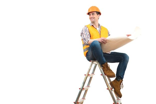 L'ingénieur heureux avec un papier assis sur l'échelle sur fond blanc