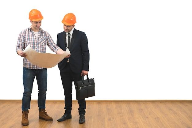 L'ingénieur et un homme d'affaires se tiennent avec un papier sur le fond du mur blanc