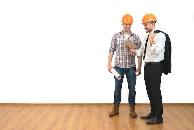 L'ingénieur et un homme d'affaires se tiennent avec une tablette sur le fond du mur blanc