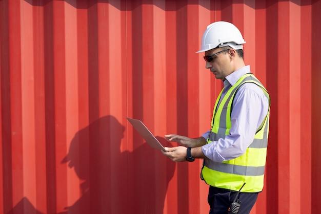 Ingénieur homme caucasien confiant portant un casque de sécurité blanc à l'aide d'un ordinateur portable et vérifier le contrôle de la boîte de conteneurs de chargement du navire de fret pour l'importation et l'exportation, le transport