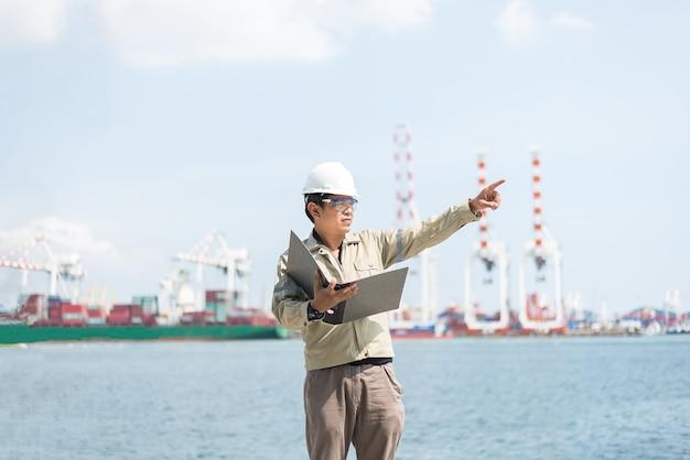 L'ingénieur homme travaillant avec conteneur cargo fret navire dans le chantier naval au crépuscule pour logistic import e