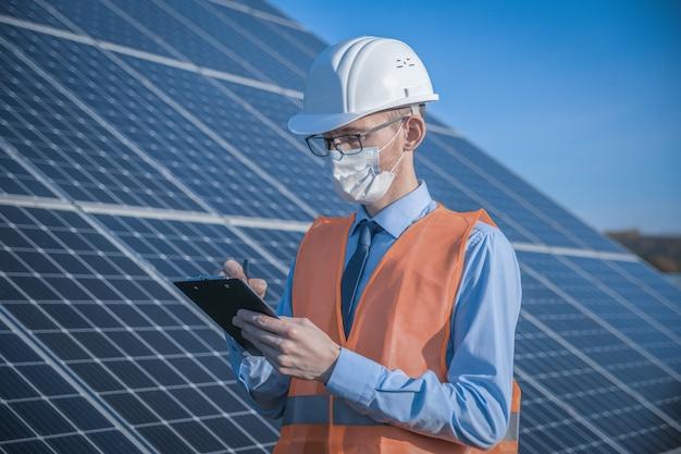 Ingénieur, homme en uniforme et masque, lunettes de casque et veste de travail sur un des panneaux solaires à la station solaire
