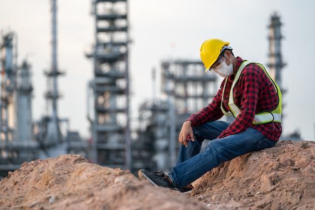 Ingénieur de l'industrie de la raffinerie portant une maladie coronavirus protectrice à partir de 2019 ou masque covid-19 triste à cause du chômage