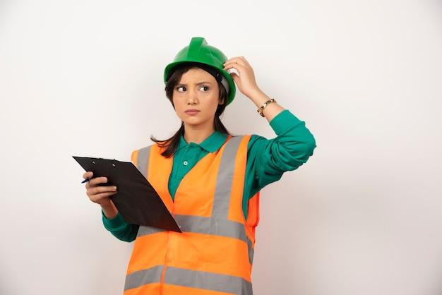 Ingénieur industriel féminin en uniforme avec presse-papiers sur fond blanc.