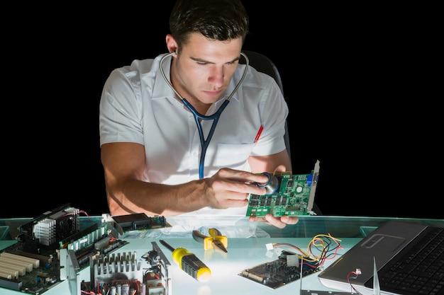 Ingénieur en informatique attrayant examinant le matériel avec stéthoscope