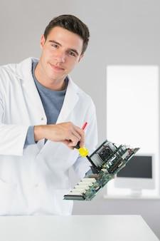 Ingénieur en informatique de contenu attrayant réparant le matériel avec un tournevis
