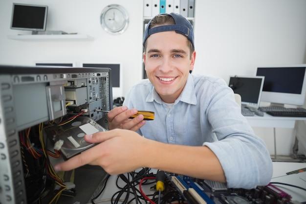 Ingénieur en informatique souriant travaillant sur une console cassée avec un tournevis